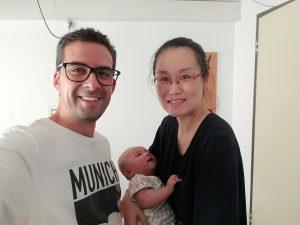 Dr. Jing Xie holding baby Huan, and Juan-Carlos
